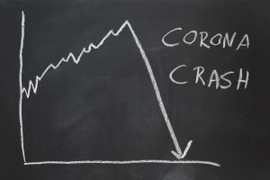 a hand-drawn graph on chalkboard showing stock market collapse with corona crash written beside it.