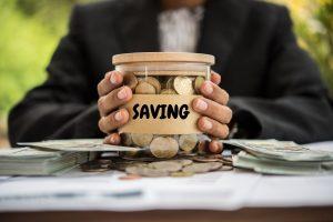 Saving Money putting coins into a jar.